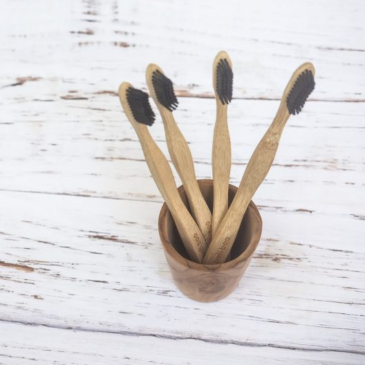 4 bamboo toothbrushes of bali boo in a wooden cup