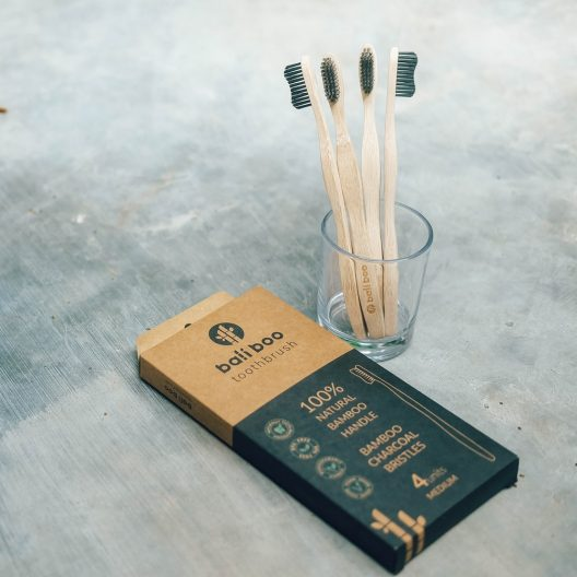 glass holding 4 bamboo toothbrushes of bali boo next to a box of 4 bamboo toothbrushes of Bali Boo